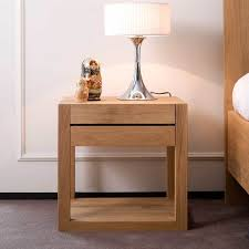 graceful wooden bedside table with single drawer and white drum table lamp shade on top on grey rug