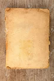 old closed softcover book with yellowed pages on a wooden background stock photo 19926343