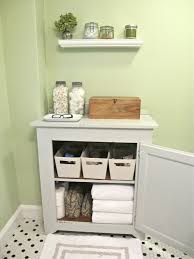 small wooden bathroom cabinet with storage baskets and shelf plus white swing door on mosaic tile floor