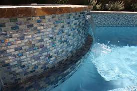 iridescent blue 1 x 2 glass tile surrounds the pool and raised spa on the rai