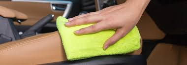 someone wiping down leather car interiors with a bright green cloth
