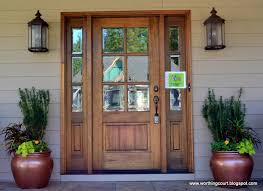 front door with sidelights, oversized exterior lights and filled containers  via Worthing Court blog