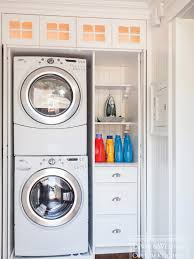 Hidden laundry closet with stackable front loading washer and dryer and  built-in storage drawers and shelves with beadboard paneling.