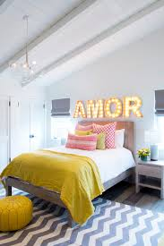 fabulous gray and yellow bedroom boasts sloped planked ceiling illuminated by a glass cer pendant over a gray toned wood bed layered in white bedding