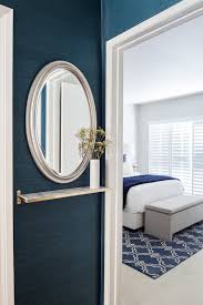 small entry foyer with blue grasscloth wallpaper mirror and floating shelf design by