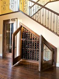 an under stairs wine storage space with lots of shelves for bottles and glass doors