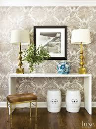 Farrow & Ball's Lotus wallpaper covers the foyer walls. Brass touches,  including Vaughan table