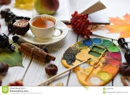 a cozy autumn photo with a cup of tea watercolors a drawing a book autumn leaves and cinnamon sticks
