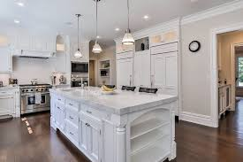 traditional kitchen with white cabinetry calacatta carrara marble countertop island