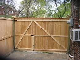 simple details for old fashioned wood fence designs with black metal lock near brick wall