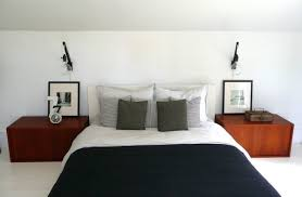 modern bedroom wall lights using clear glass lamp shades above retro electric alarm clock over red bedside wall lighting