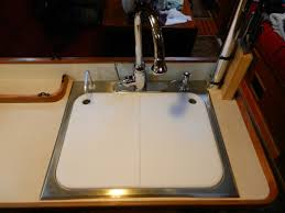 the cutting boards are d behind the sink and next to the stove to control any splashing that may occur from the faucet or stove