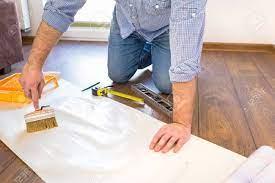 Handyman Applying Glue For A Wallpaper ...