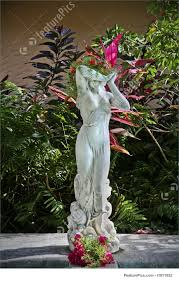 statue of women with her hands together and a flower piece on top of her head