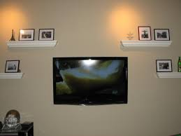 tv on wall with shelves. wall mounted flat screen tv surrounded by white wooden floating shelves, stylish mount tv on with shelves