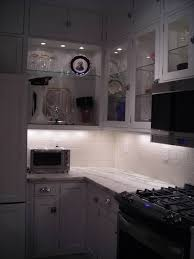 lighting for cabinets. picture of glass front kitchen cabinets with decorative puck lights inside lighting for t