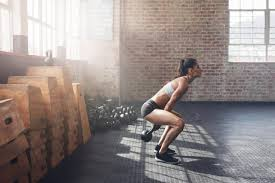 side view of tough young woman exercising with kettle bell at gym fit female athlete