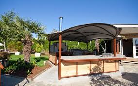 covered outdoor kitchen with unique roof and chimney also stainless steel sink plus faucet