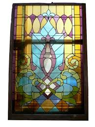 this is a striking large antique american jeweled stained glass window circa 1900 with an abstract design featuring stylized fleurs de lis