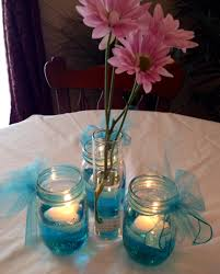 Wedding or baby shower table decorations: Mason jar with filled with water,  1 drop food coloring, floating candle & ribbon. Bud vase with daisies.
