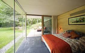 bedroom with glass walls and green views