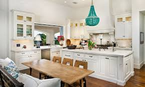 white kitchen with turquoise chandelier over island