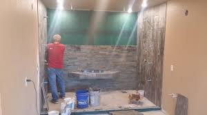 porcelain slate look tile on side walls and natural dry stack slate back wall with custom floating bench