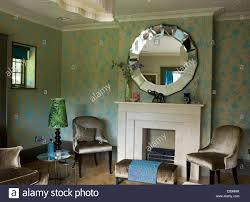 mirror above fireplace. round mirror above fireplace in traditional sitting room with grey velvet upholstered chairs and stool v