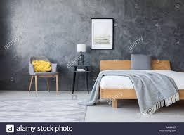 Poster Auf Beton Wand über Hocker Mit Lampe Und Bett Aus Holz In