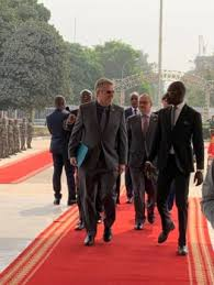 ambador simon henshaw and deputy chief of mission hugues ogier arrive at president condé s office to present his credentials