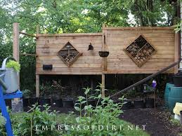 two privacy screen panels with bug hotels in garden