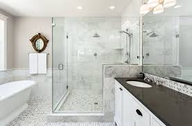 luxury white marble bathroom with large glass walk in shower white vanity with black countertops