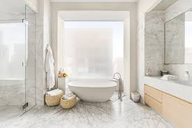 the two light filled master bathrooms feature marble floors and walls
