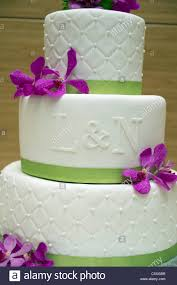green and white wedding cakes. a wedding cake with purple flowers, white ganache and green ribbon the letters l n on front. cakes