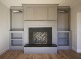 living room fireplace boasts a gray fireplace wall ed with a gray fireplace mantle and black fireplace surround hearth flanked by gray built in cabinets