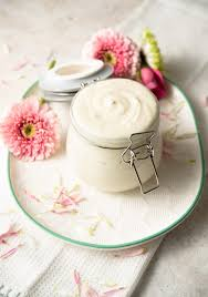 a glass jar of homemade lotion on a white plate with flowers around it