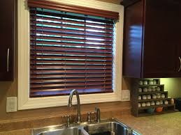 graber lake forest faux wood blinds are a great touch for over the kitchen sink