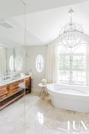 beautiful bathroom features a danville sphere chandelier hanging over an oval freestanding tub placed in front of windows dressed in ivory ds
