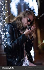 attractive young man in sunglasses and leather jacket smoking cigarette under garland on city street at night stock image