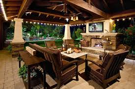 orange county outdoor patio design with bordered cushions and pillows terranean stacked stone fireplace wood furniture