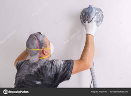 plasterer wearing dust mask polishes wall sanding machine house renovation stock photo