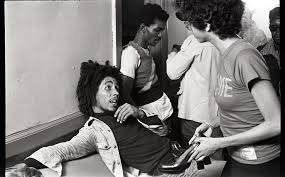 Bob Marley and the Wailers at Paul's Mall: Marley backstage speaking with a  woman, in background Carlton Barrett, Aston Barrett, and Joe Higgs, July  1973