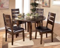 simple small dining room arrangements ideas with round dining table with leaf and 4 wooden chairs with black leather cushions on carpet tiles