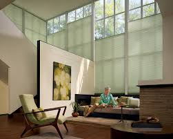 Sheer window treatments for a large loft window allows light to filter in  yet still provides