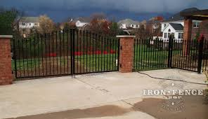 fence next to driveway. custom 4ft arching to 5ft iron driveway gate mounted on brick pillars with matching fence next r
