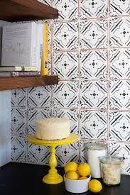 stick wall tiles quotxquot: black and white kitchen features a soapstone countertop and a white and black quatrefoil tile backsplash adjacent to a wall lined with stacked wooden