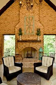 cedar mantle brick fireplace chairs table flowers chandelier antique look white ceiling interior design