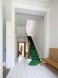 white room with bright green runner rug on the staircase puddling at base