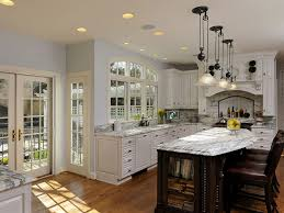 kitchen remodeling tips with addition of marble countertop on island and cabinets decorated with ceiling lights and traditional pendant lamps plus