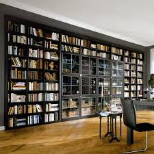 Breathtaking Home Library Featuring Huge Wall Bookshelf With Glass Doors  And Chevron Wooden Floor Plus Black Leather Chair